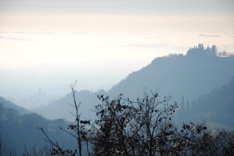 La piana di Caprino avvolta dalla nebbia. Sulla destra, i cipressi delle Terre Rosse, in basso si intravede in campanile della chiesa parrocchiale di Caprino.